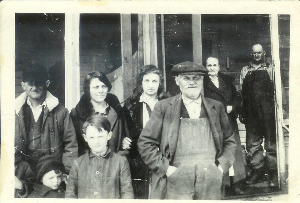"(From left to right) The three kids in the front: Gilbert George ""Red"" Schmidt (1919-1989) (only his elbow and hand are visible in the bottom left corner of the photograph); Roland Richard ""Dick"" Schmidt (1921-1985); William Henry ""Bill"" Schmidt (1912-1982). The adults in the back: William Conrad Schmidt (1888-1956); Anna Henrietta (Niewoehner) Schmidt (1887-1942); Gertrude (Niewoehner) Arnold (1885-1973); Georg Karl Schmidt (1864-1933); Anna Margaret ""Maggie"" (Lindemann) Schmidt (1864-1943); Edward Dietrich Schmidt (1890-1943). This photo was taken at the Schmidt family farm in Ellington Township, east of Mallard and west of West Bend. Photo courtesy of Cindy (Springer) Schmidt."