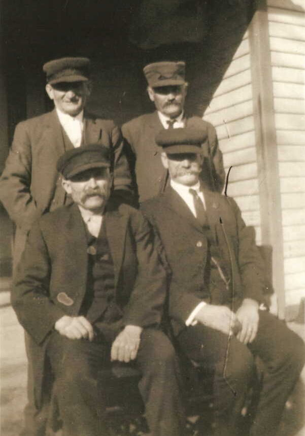 "(Left to right) (Back row) Henry John Schmidt, Georg Karl ""Charles"" Schmidt. (Front row) Michael ""Mike"" Lindemann, John A. Lindemann. (Henry and Karl were first cousins. Mike and John were also first cousins. The Schmidt men were also more distant cousins of the Lindemann men. Mike Lindemann's sister, Maggie, married Karl Schmidt. Mike's wife, Lizzie, was Henry Schmidt's sister. John A. Lindemann, Mike's cousin from Iowa City, often left off an ""n"" from his last name and spelled it ""Lindeman"".) Photo courtesy of Denise Lindemann."